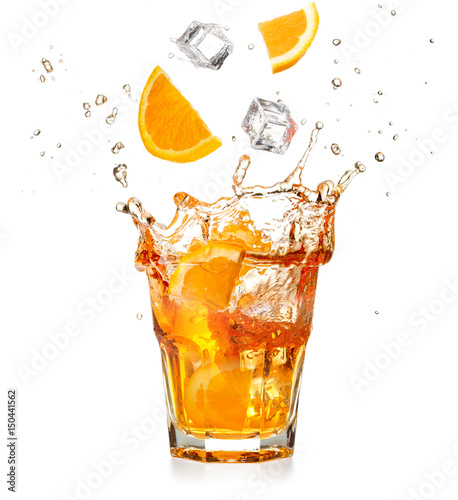 orange slices and ice cubes dropping into a splashing cocktail