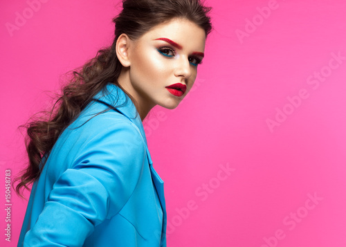 Beautiful girl in blue suit on pink background with creative make-up and fashionable style. Beauty face. Photo taken in the studio.