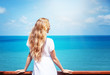 young woman in a white dress with long blond hair admires the bright blue sea