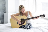 Smiling woman with guitar sitting on the bed