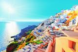 Breathtaking scenery of Oia village traditional Greek island architecture at Aegean sea and noon zenith sun flare background. Santorini island, Greece, Europe. Santorini is famous and popular resort.