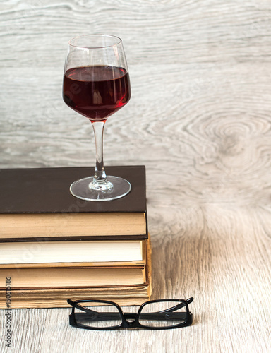 A glass of red wine and books on the table. The concept of rest
