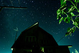 Silhouette of a country house against the background of the starry night sky and the Milky Way galaxy
