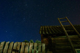 Village. Old wooden ladder leaning against the barn with a slate roof in the night star sky. The staircase leads to the sky.
