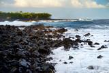 Beautiful pink tinted waves breaking on a rocky beach at sunrise on east coast of Big Island of Hawaii