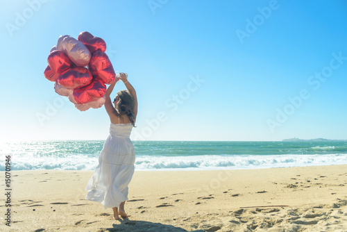 Poster Young woman in white dress with red balloons on the beach