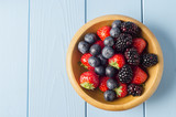 Mixed Berry Fruits in Wooden Bowl on Light Blue Wood Planked Table from Above - 150722742