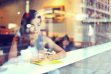 Fototapety Cafe city lifestyle woman on phone drinking coffee texting text message on smartphone app sitting indoor in trendy urban cafe. Cool young modern mixed race Asian Caucasian female model in her 20s.
