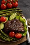 Grilled beefsteak with asparagus and vegetables on black background.