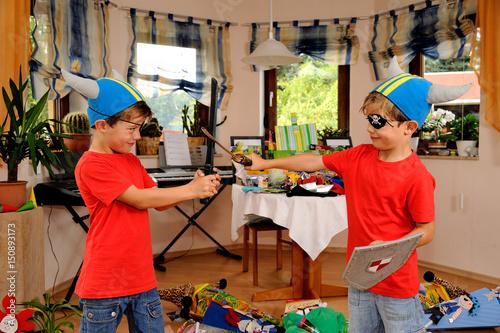Zwei Zwillinge haben sich verkleidet als Pirat, Wickinger und Ritter kämpfen mit Poster