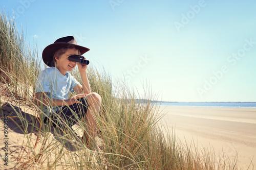 Child explorer with binoculars at the beach