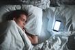 Donna dorme con smartphone accanto, stress da lavoro