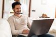 Smiling man using his laptop computer