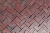 Texture of a red paving stone lined with zigzag - wave