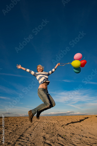 Poster Carefree girl jumping with colorful balloons