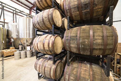 Staande foto Industrial geb. Stack of barrels in cellar with stainless steel brewing equipments in a modern microbrewery in America.