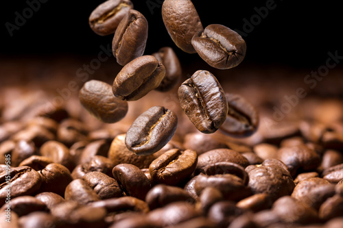Falling coffee beans close-up, flying coffee beans over dark background
