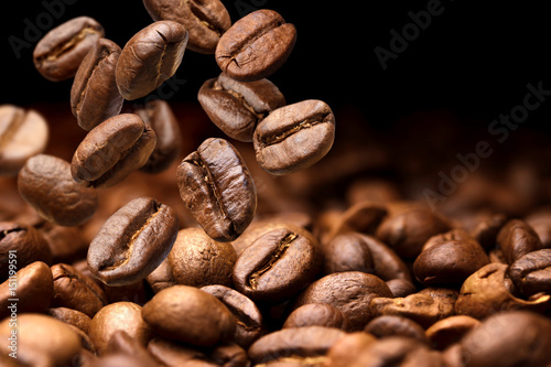 Fototapeta Falling coffee beans. Dark background with copy space, close-up