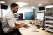 Focused businessman using desktop pc in office