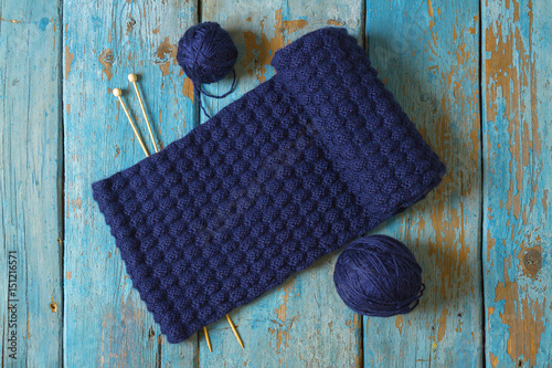 Two coils of wool, knitting needles and a blue knitted scarf Poster