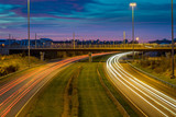 sunset sky highway with light trails cars passing fast carriage way modern lighting busy intersection traffic