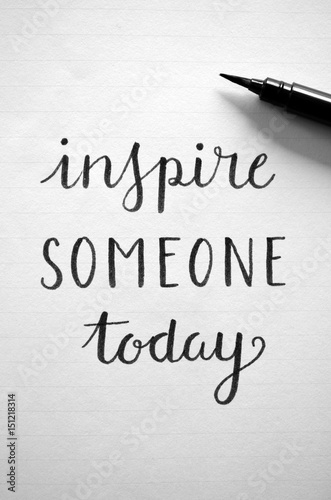 Poster INSPIRE SOMEONE TODAY written in notepad on desk