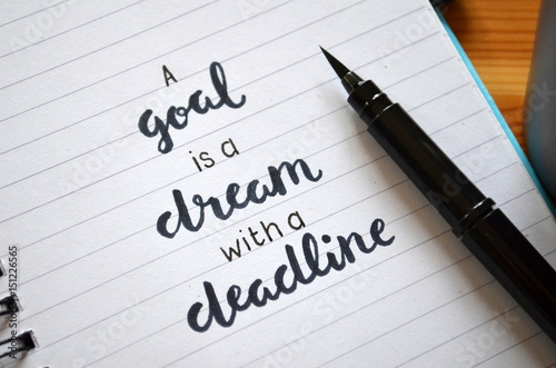 A GOAL IS A DREAM WITH A DEADLINE written in notebook on desk Poster