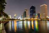 Benjakitti public park in Bangkok city in the twilight with skyscrapers and lights reflecting in the lake.