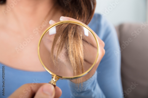 Woman Looking At Her Hair Through Magnifying Glass