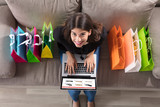 Woman With Shopping Bags Using Laptop
