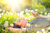 Beautiful young woman lying on the field in green grass and blowing dandelion - 151326797