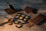Chocolate bar pieces with cocoa powder.  Background with chocolate. Slices of chocolate,  Copyspace