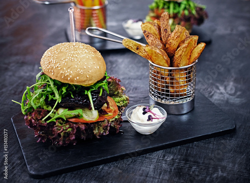Poster Vegan mushroom burger with salad on a table.