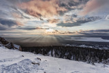 Winter landscape in the mountains. Clouds in the sky, sunny day. Lots of snow, frost, cold space. Ural Mountains, Russia. Sunset in the mountains