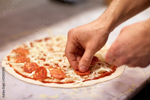 cook hands adding salami to pizza at pizzeria Poster