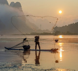 Cormorant fisherman throws a net with ancient traditional chinese bamboo boats at sunrise - China