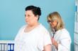 Übergewichtige Frau wird von Ärztin untersucht