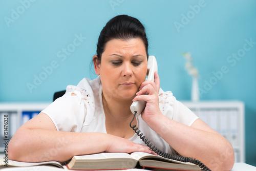 überforderte frau am telefon schaut ins buch Poster