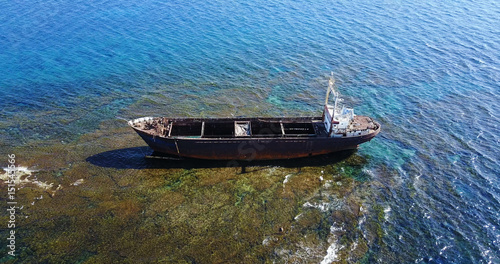 Beautiful seascape with old big, broken, rusty boat near the coast of Peyia, Cyprus. Ship graveyard. Famous landmark in the Mediterranean sea.