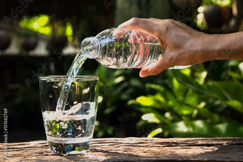 Żeńska ręki dolewania woda od butelki szkło na natury tle