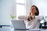 Excited woman working at desk in office. Using antistress ball. - 151612351