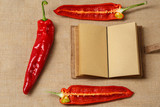 Red Chili Pepper and Notebook lying on a sackcloth surface