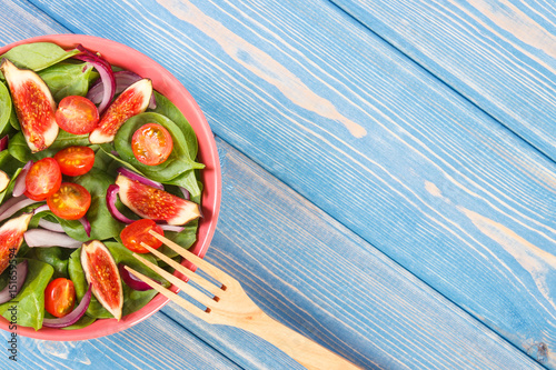 Fruit and vegetable salad with wooden fork, concept of healthy nutrition, copy space for text on boards