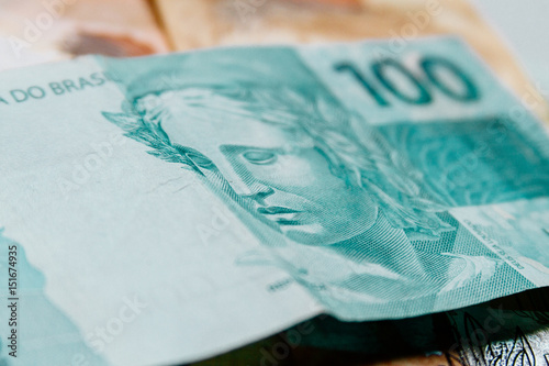 Poster Macro closeup of a 100 Brazilian reais banknote on 50 reais notes on background