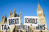 Hands holding signs protesting modern British social issues like Brexit, tax, education, defense, and health in front of the Houses of Parliament at Westminster Palace in London, United Kingdom - 151762383