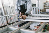 Factory for aluminum and PVC windows and doors production. Manual worker assembling PVC doors and windows. Selective focus.  - 151775100