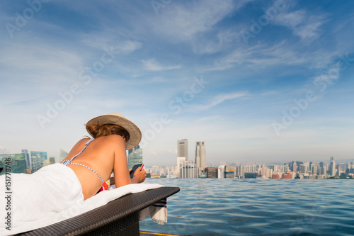 Lady in Bekiny relax and use mobule phone in swimming pool on hotel rooftop Poster