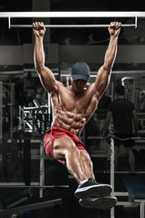 Muscular man working out in gym, doing stomach exercises on a horizontal bar, strong male naked torso abs