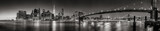 Panoramic Black and white view of Lower Manhattan Financial District skyscrapers at twilight with the Brooklyn Bridge and East River. New York City - 151800108