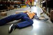 Fallen worker lying on the floor in aisle between storage shelves